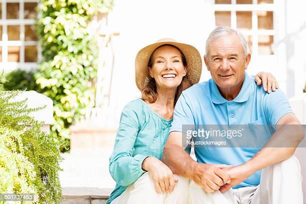 Feliz mujer Senior brazo de estar cerca de hombre en el jardín