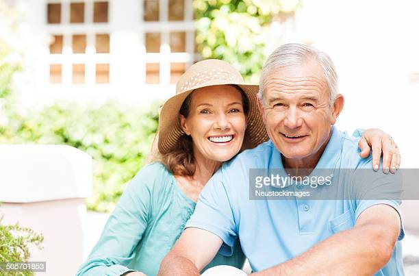 Happy Senior Woman Siting Arm Around Man In Garden