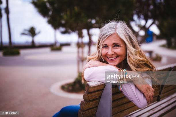 公園のベンチに座って満足している年配の女性