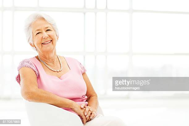 Happy Senior Woman Sitting On Chair At Home