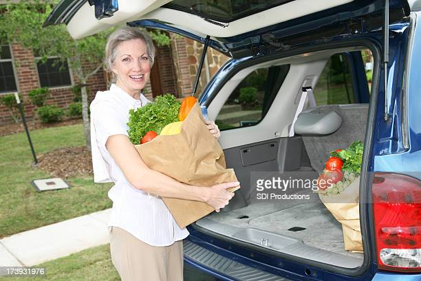 Happy Senior Woman Taking Groceries Out Of Car