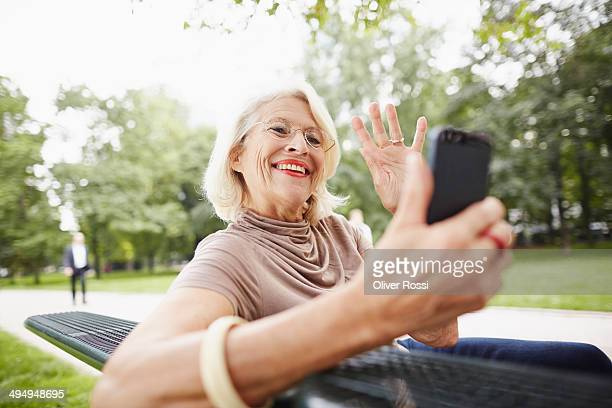 Happy senior woman taking selfie on park bench