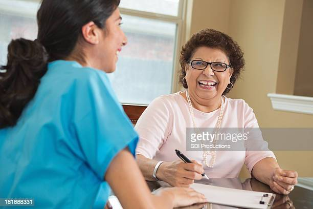 Happy senior woman talking with home healthcare worker