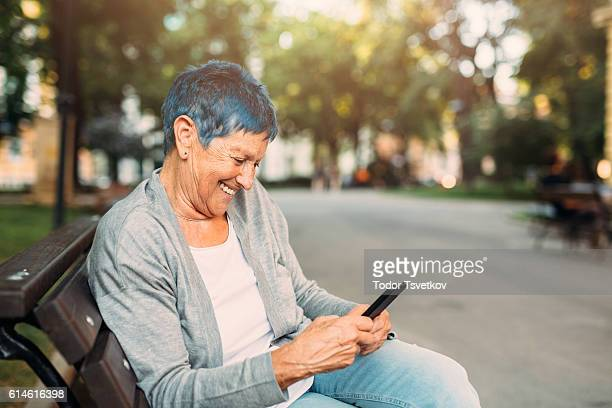 Happy senior woman texting
