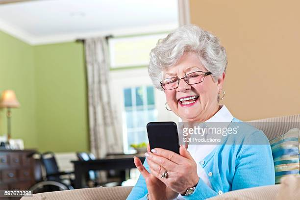 Happy senior woman uses smart phone to send text