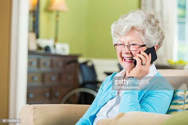 Happy senior woman uses smart phone to talk with family