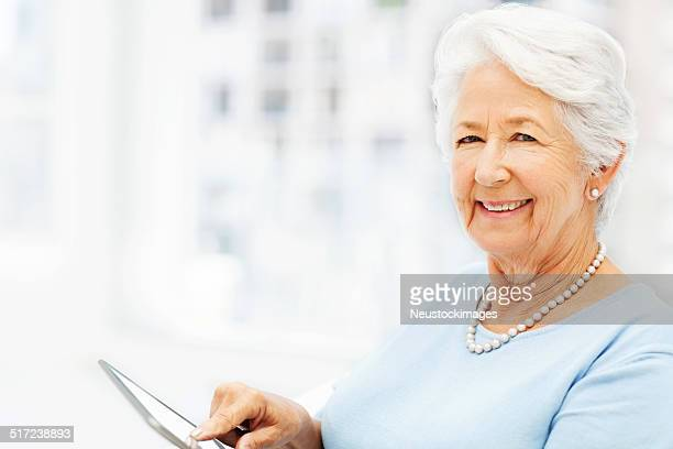 Happy Senior Woman Using Digital Tablet