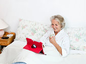 Happy senior woman using digital tablet while having coffee on bed at home