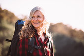 Cheerful active senior woman with grey hair carrying backpack and hiking in nature