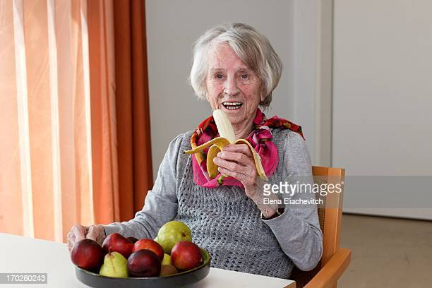 Happy senior woman with bowl of fruit and a banana