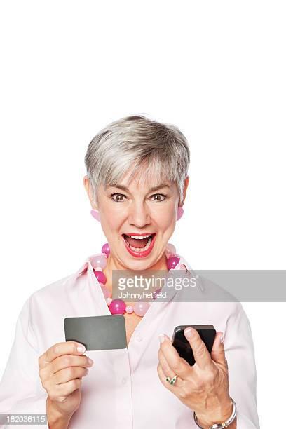 Happy Senior mujer con tarjeta de crédito y teléfono