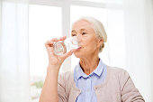 age, health care and people concept - happy senior woman with glass of water at home