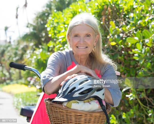Happy Senior Woman with Long Hair Head Shot with Bicycle Looking a Camera