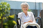 Happy senior woman sitting on wheelchair and recovering from illness. Handicapped mature woman sitting in wheelchair smiling and looking at camera. Portrait of a disabled elderly woman outdoor in a nu