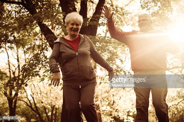 Happy seniors couple in sports clothing enjoying together in nature.