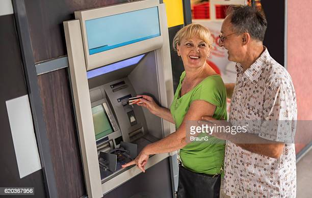 Happy seniors withdrawing money from a cash machine.