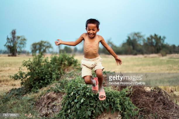 Happy Shirtless Boy Jumping On Field Against Sky At Farm