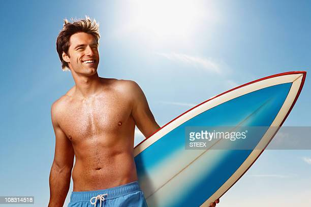 Happy shirtless guy with a surfboard on sunny day