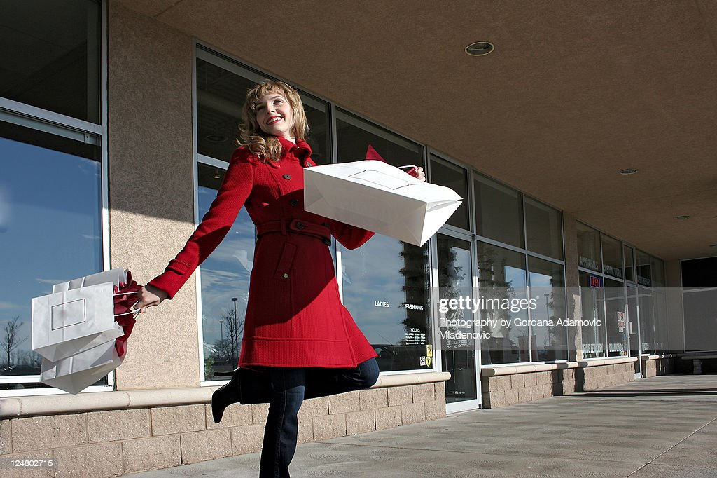 Happy shopper in red coat : Stock Photo