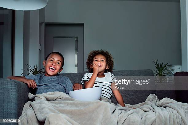 Happy siblings having popcorn while watching TV