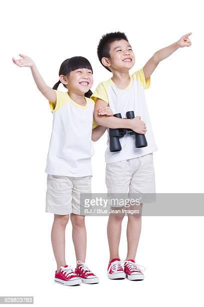 Happy siblings holding telescope