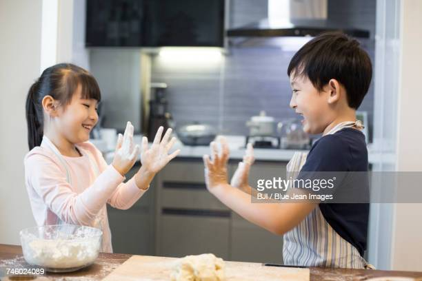 Happy siblings playing with flour