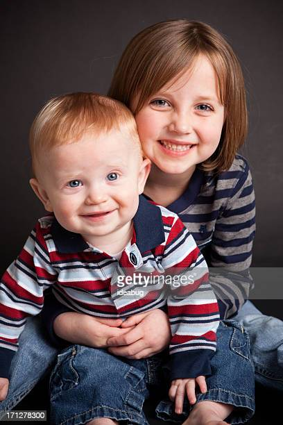 Happy Sister Holding Her Baby Brother, With Black Background