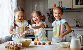 happy sisters children girls bake cookies, knead dough, play with flour and laugh in the kitchen