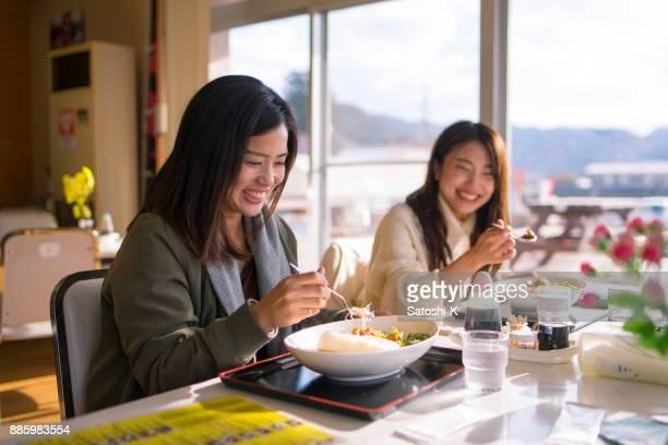 明るいレストランで昼食を食べて幸せな姉妹