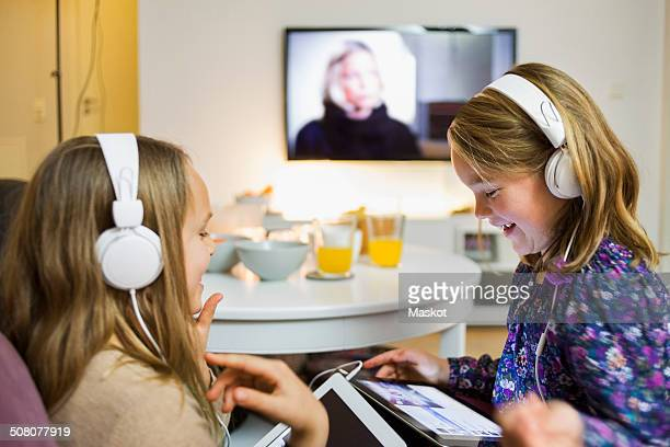 Happy sisters listening music on digital tablets in living room