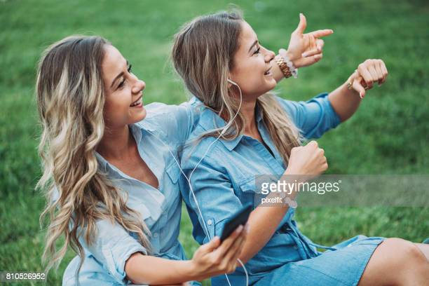 Happy sisters listening music together