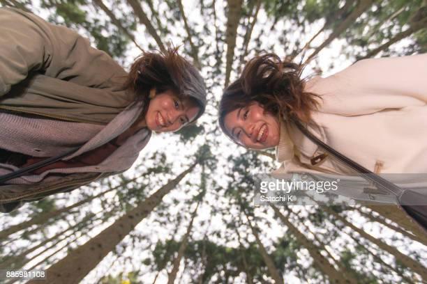 森林の地面にカメラを見て幸せの姉妹