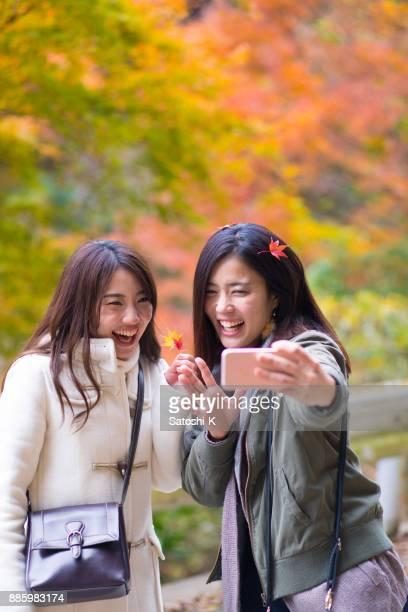 紅葉の selfie 写真を撮る幸せな姉妹