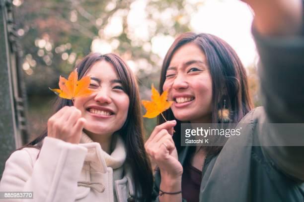 落ち葉で selfie 写真を撮る幸せな姉妹