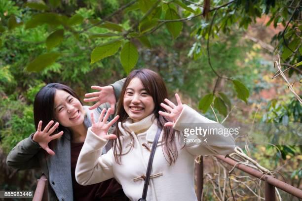 緑の森に手を振って喜んで姉妹