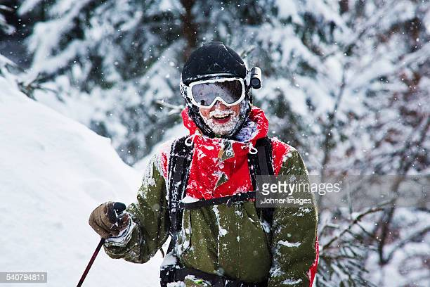 Happy skier covered by snow