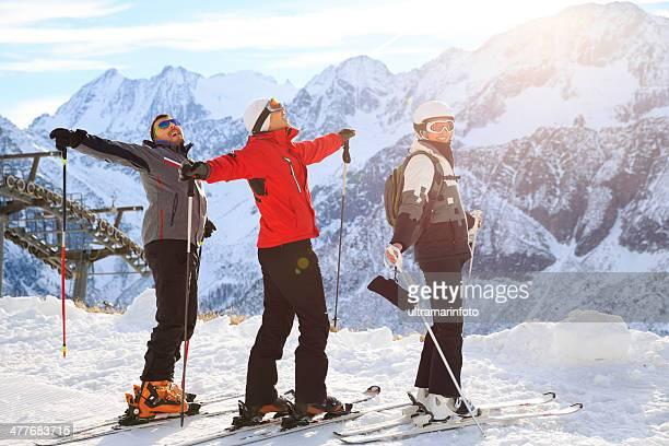 Groupe heureux de ski au sommet de la montagne