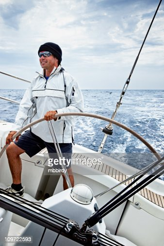 Happy skipper driving sailing ship in bad weather