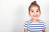 Happy small girl on the grey light background in the studio.