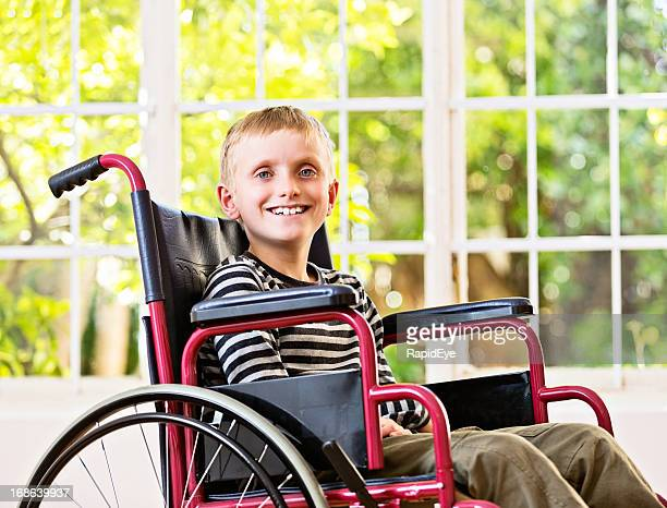 Happy, smiling 9-year-old boy sitting in wheelchair by window