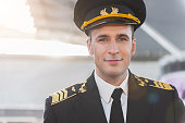 Confident aviator wearing special uniform is glancing at camera with light smile. Portrait. Copy space on left side