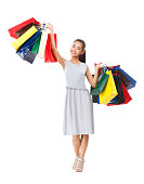 Happy smiling Asian woman standing in summer clothes and waving shopping colorful bags. Isolated photo for holiday shopping, store sales, discounts and gifts theme and other advertising projects
