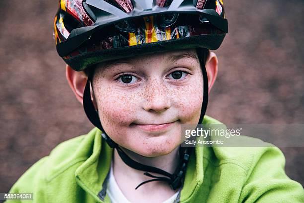 Happy smiling boy wearing a bicycle helmet