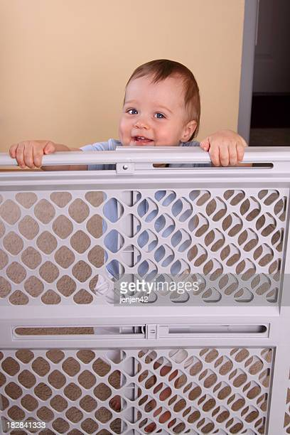 A happy smiling child over a child proofing fence
