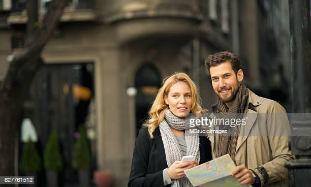 Happy smiling couple exploring new city.