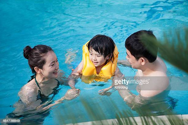 Happy smiling family teaching son how to swim in the pool