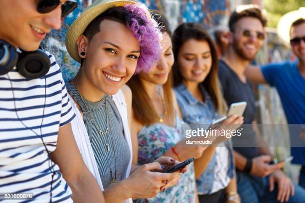 Happy smiling friends with smart phones standing against wall