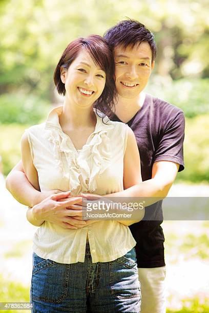 幸せな笑顔のヘルシーなマチュア日本のカップルに包み込む東京の公園