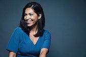 Happy smiling hispanic businesswoman looking away over shoulder. Studio Shot Portrait. Dark grey background.