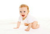 Happy smiling little baby crawls on a white background